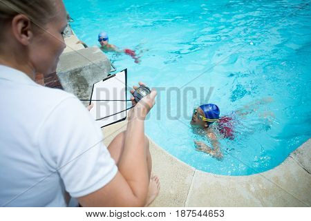 High angle view of female instructor monitoring time of children swimming in pool