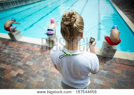 Rear view of female instructor monitoring children at poolside