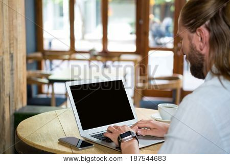 Side view of young man using laptop in coffee shop