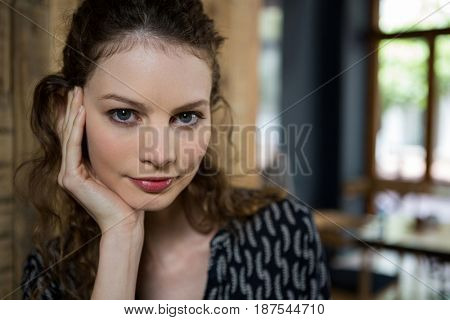 Portrait of beautiful young woman with hand on chin in cafe