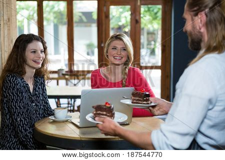Male barista serving dessert to female customers in coffee shop
