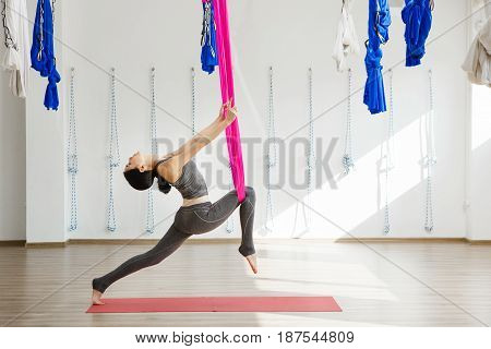 Girl stretching legs with help of hammock. Aerial exercise or antigravity yoga indoors, woman jumps and does aero poses with head leaned to back