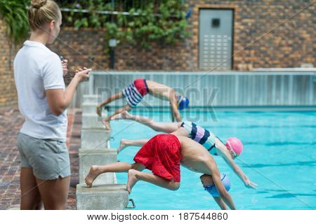 Side view of female instructor monitoring time at poolside