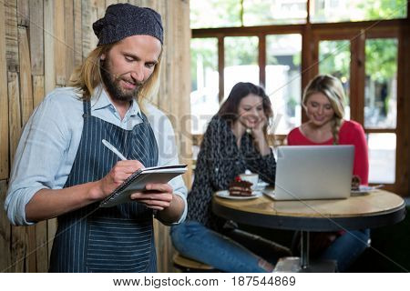 Male barista writing orders with female customers in background at coffee shop