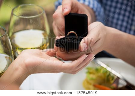 Close-up of man giving engagement ring to woman at outdoor restaurant