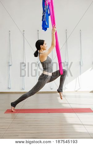Girl stretching legs with help of hammock. Aerial exercise or antigravity yoga indoors, woman jumps and does aero poses with head leaned
