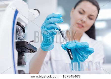 Measuring bottle. Delighted medical worker holding test glass in left hand while taking examples and going to examine them