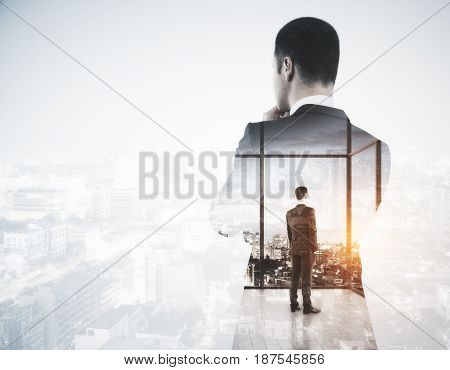 Back view of young businessman looking into the distance on light city background with copy space. Employment concept. Double exposure