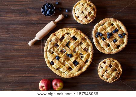 Homemade pastry apple pie pies bakery products on dark wooden kitchen table with raisins, blueberry and apples. Traditional dessert on Independence Day. Flat lay food background. Top view