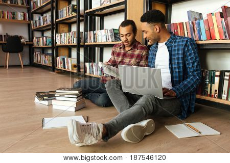 Picture of young concentrated two african men students sitting in library reading books using laptop computer. Looking aside.