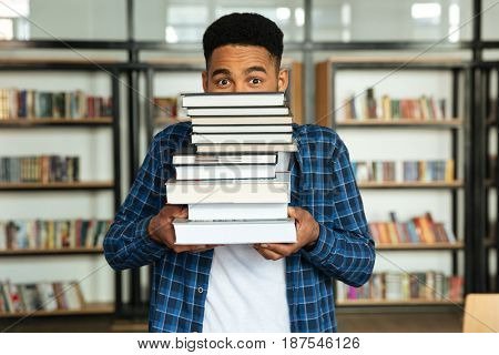 Portrait of a young afro american male student holding stack of books while standing in a library