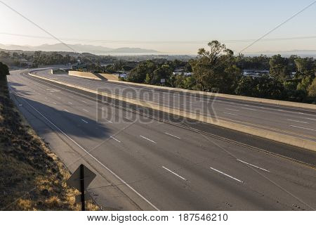 Empty ten lane freeway at sunrise in the San Fernando Valley area of Los Angeles, California.