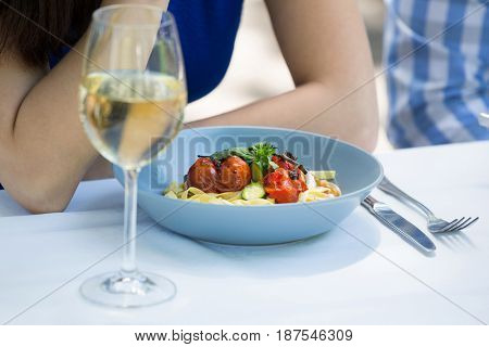 Cropped image of couple with food and wineglass on table at restaurant