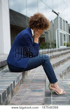 Depressed businesswoman sitting in the office premises
