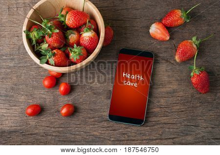 kitchen table with fresh strawberry and health care text on screen smart phone healthy eating and dieting food concept of health care Image focus top view.