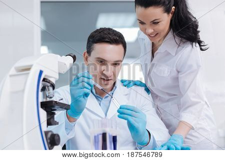 Concentrate on process. Confident scientist holding medicine dropper in right hand while pouring down assay reagent into test glass, keeping mouth opened