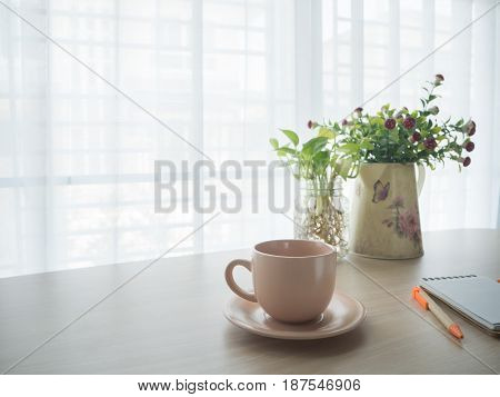 office table with hot coffee cup beautiful flower on pot notepad paper and pencil on blurry beautiful white drape window texture background.