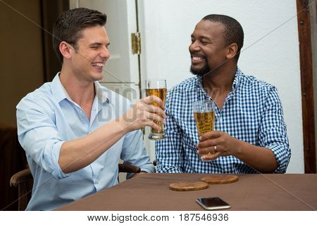 Cheerful male friends toasting beer glasses in restaurant