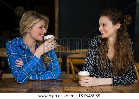 Smiling young female friends having coffee while talking in cafe