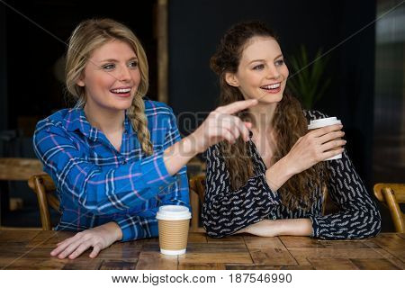 Smiling young woman showing something to friend in coffee shop