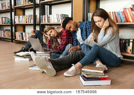 Image of young tired students sitting in library on floor using laptop computer and reading books while writing notes. Looking aside.