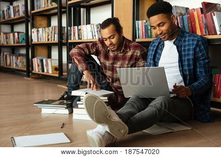 Image of young two african men students sitting in library reading books using laptop computer. Looking aside.