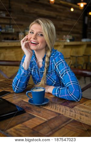 Portrait of cheerful young woman sitting at table in coffee shop