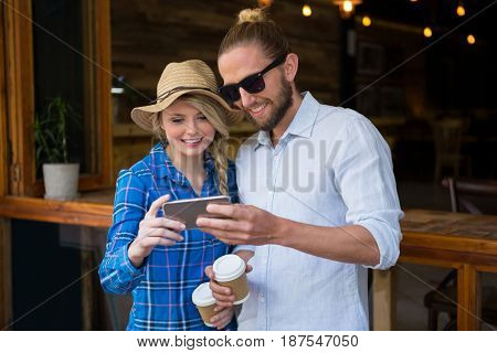 Smiling young couple using smart phone in coffee shop