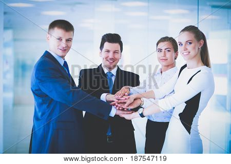 Business team joining hands together standing in office
