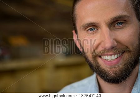 Close-up portrait of young man smiling in cafeteria