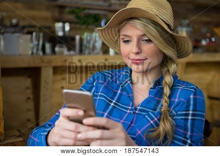 Young woman wearing hat while using mobile phone in coffee shop