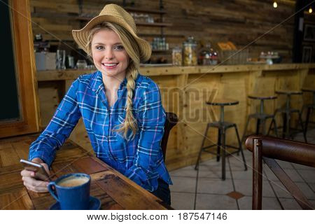 Portrait of young woman wearing hat while holding mobile phone in coffee shop