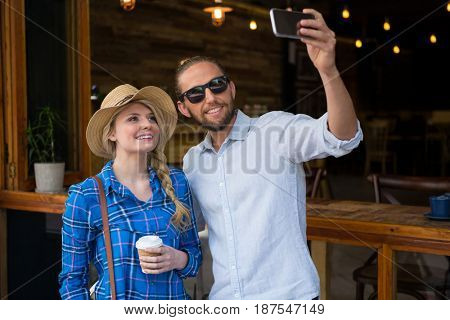 Smiling young couple taking selfie with mobile phone in coffee shop