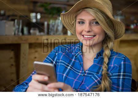 Portrait of smiling young woman wearing hat while using mobile phone in coffee shop