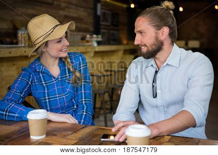 Smiling young couple talking at table in coffee shop
