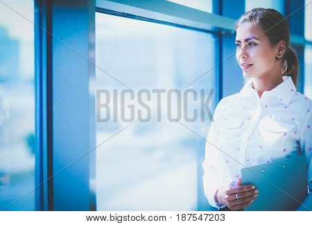 The businesswoman stand near the panoramic window
