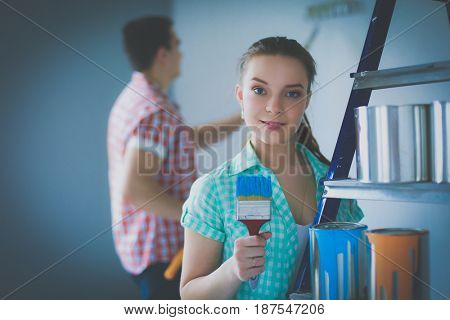 Portrait happy smiling young couple painting interior wall of new house