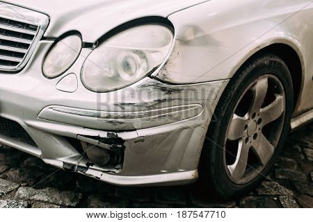 Broken Bumper Luxury Car Scratched With Deep Damage To Paint. Abandoned Car After Accident In City Street