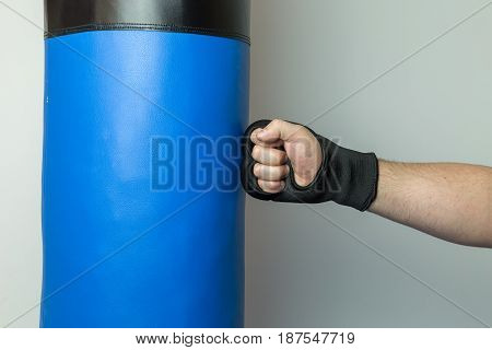Martial Artist Wearing Black Gloves Punching Straight On A Blue Punching Bag