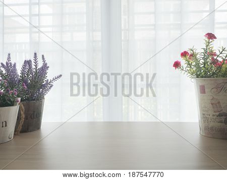 office table with variety of flower frame on pot pink flower purple lavender flower with blurry beautiful white drape window texture background.