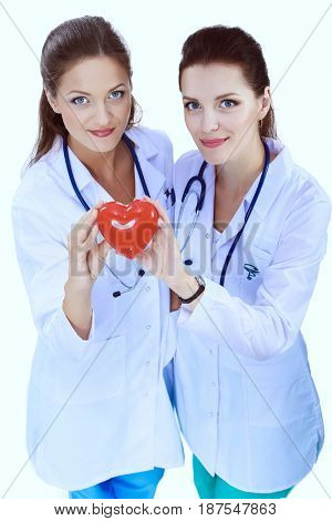Two woman doctor holding a red heart, isolated on white background