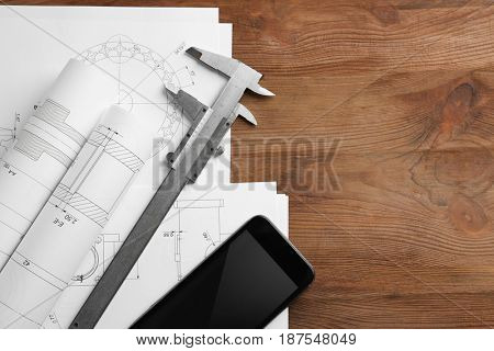Calipers, phone and blueprints on engineer's workplace