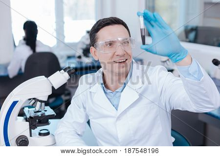 Good mood. Happy scientist wearing protective glasses and expressing positivity while looking at test tube