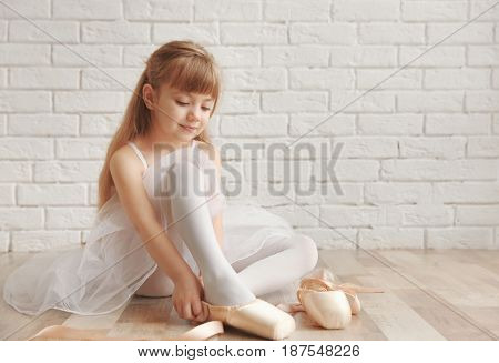 Beautiful little ballet dancer putting on pointe shoes in light dance studio