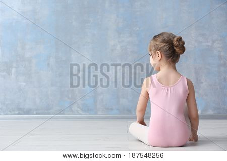 Cute little ballerina sitting on floor in dance studio