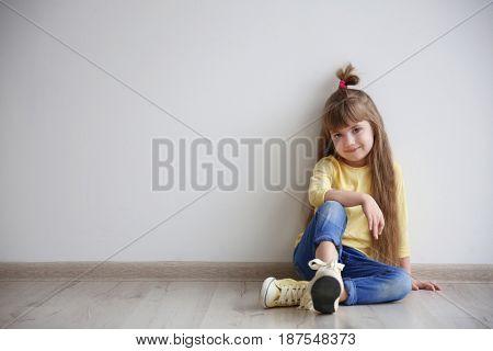 Little fashion girl sitting on floor in light room