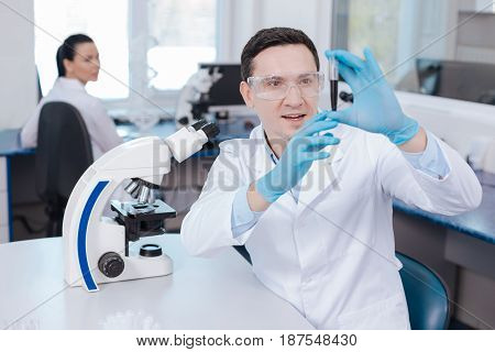 Facial expressions. Delighted male person sitting at his workplace, raising both hands while keeping mouth opened