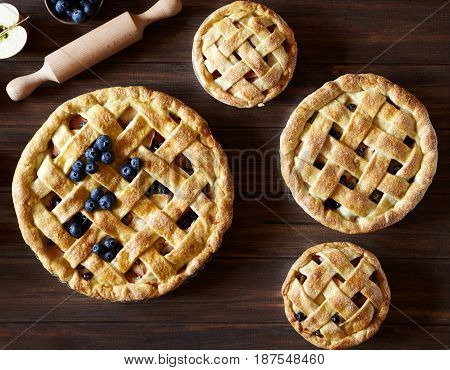 Close up. Homemade pastry apple pie pies bakery on dark wooden kitchen table with raisins, blueberry and apples. Traditional dessert on Independence Day. Flat lay food background. Top view