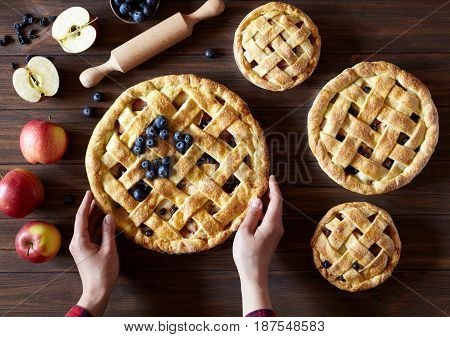 Apple pie on the kitchen wooden table with apples, raisins, blueberry and rolling pin. Hands in the frame. Traditional dessert for Independence Day. Dark food photo. Flat lay bakery food background.