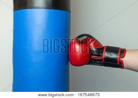 Boxer Wearing Red And Black Boxing Gloves Punching Straight On A Blue Punching Bag